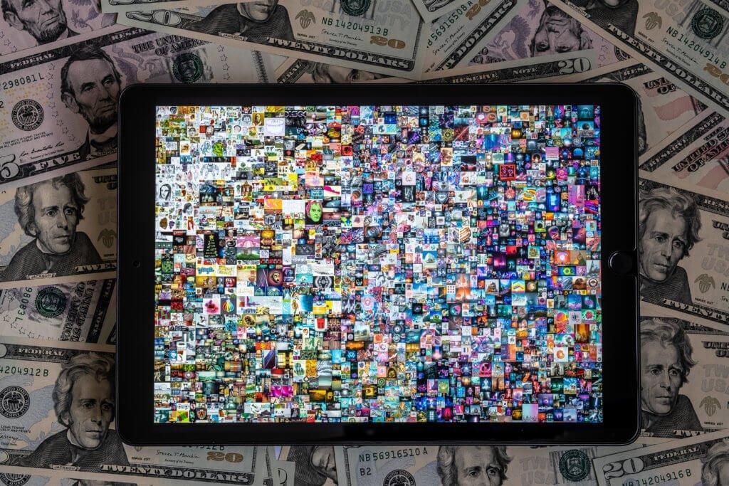 """Au centre de la tablette, l'œuvre """"Everydays : The First 5,000 Days"""" de l'artiste Beeple"""